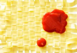 Ketchup on a mat of woven pasta