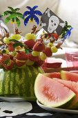 Colourful fruit kebabs stuck in a watermelon for a pirate-themed party