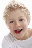 A little boy eating raspberries