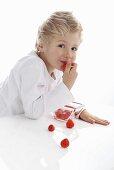 A little boy eating fresh strawberries