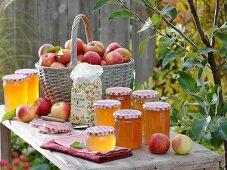 Jars of apple jelly, basket of fresh apples