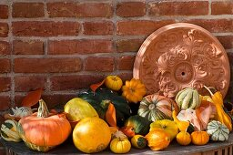Terracotta rosette, pumpkins and squashes by brick wall
