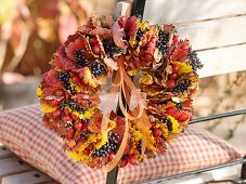 Wreath of autumn leaves and rose hips on chair back