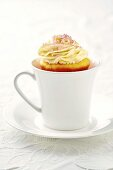 Mango cupcake in a cup and saucer