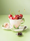 Cherry jam on spoon, fresh cherries in cup and saucer