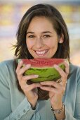Young woman holding a slice of watermelon in her hand