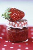 A strawberry on a full jam jar