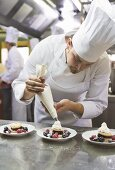 Chef piping cream onto berry desserts