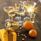 Orange with sparkler, chocolates, glasses of sparkling wine