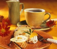 Sponge roll with orange & cream filling & a cup of coffee