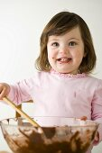 Small girl stirring cake mixture in bowl