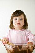 Small girl stirring cake mixture