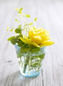 Table decoration of spring flowers in a glass of water