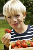 Blond boy with strawberries, one with a bite taken