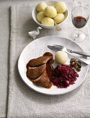 Roast goose with port wine sauce, red cabbage and potato dumplings