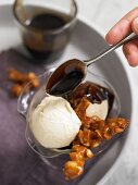 Drizzling chocolate sauce over orange sorbet with macadamia nut brittle