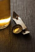 A beer bottle, cap and a bottle opener