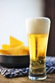 A glass of lager in front of a plate of tortilla chips