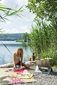 A young woman having a barbeque on a lakeside