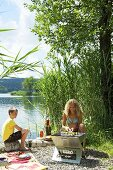 A woman and a boy having a barbeque on a lakeside