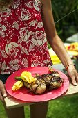A woman serving marinated grilled chicken with courgette flowers