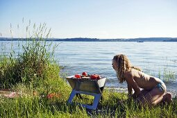 A young woman barbequing by a lake
