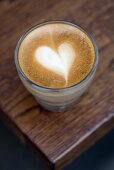 A glass of cappuccino with heart-shaped milk froth