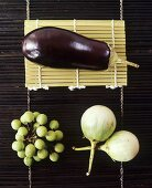 Three different types of aubergine on bamboo mat