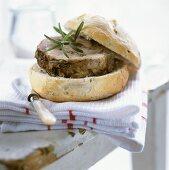 Slice of rolled pork roast in bread roll, rosemary