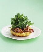 Cheese and potato cake with bacon and rocket