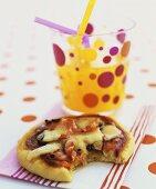 Mini-pizza with a glass of orangeade