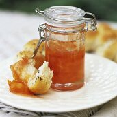 Apricot jam in a preserving jar with poppy seed roll