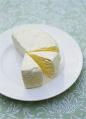 Soft cheese, two pieces cut, on a plate