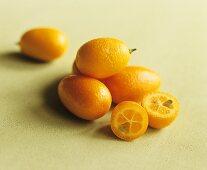 Several whole kumquats and one halved kumquat