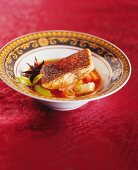 Fried sea bass with exotic spices on vegetables