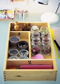 Office supplies in containers in cutlery box