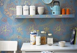 Wallpapered kitchen with shelf, cabinet and crockery