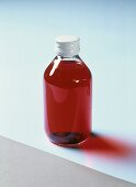 Glass bottle containing red medicine