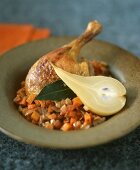 Duck leg on a bed of vegetables with pear