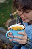 A girl with a cup of cream of pumpkin soup in a cup