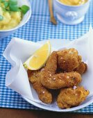 Bavarian fried chicken, potato salad and mustard behind