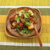 Potato, chorizo and rocket salad on wooden plate