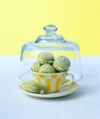 Green tea macarons with icing sugar in a cup and saucer