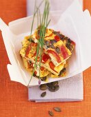 Tortilla with red pepper and pumpkin seeds in cardboard box