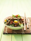 A bowl of stir-fried beef with ramsons (wild garlic, close-up)