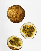 Whole and halved passion fruit against white background