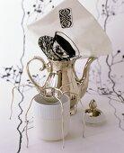 Silver teapot, tea strainer, tea beaker and printed napkin