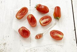 San Marzano tomatoes on paper, some hollowed out