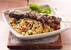 Lamb kebab on a bed of couscous with vegetables