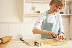 Child cutting out biscuit
